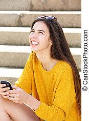 pociągający, młoda kobieta, posiedzenie na kroczy, dzierżawa cellphone