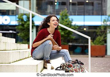 pociągający, młoda kobieta, posiedzenie na kroczy, z, notatnik, i, uśmiechanie się