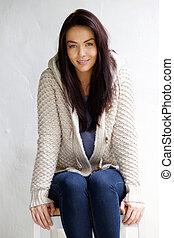 pociągający, młoda kobieta, w, wełna, sweter, posiedzenie na krześle