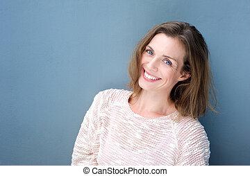 pociągający, uśmiechanie się, średni dorosły, kobieta, na, błękitne tło