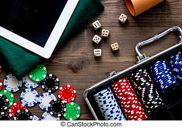 Pocker set in a metallic case nearby tablet on a wooden table top view