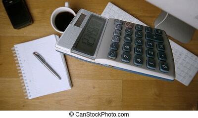 Pocket calculator falling onto office desk beside coffee...