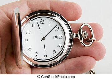 A male hand holding a fancy pocket watch