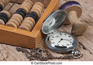 pocket watch, abacus and stamp on a wooden table
