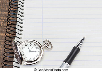 Pocket watch ballpoint pen on notebook for notes close-up.