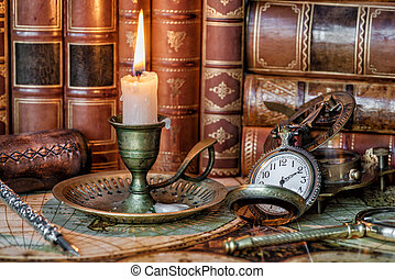 Pocket watch, burning candle and old books