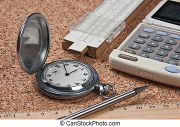 pocket watch, calculator and slide rule on a cork board