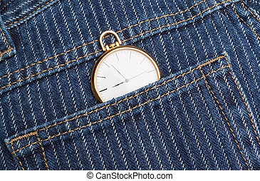 Pocket watch in a jeans pants. Closeup.