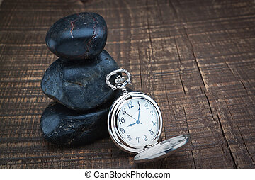 Pocket watch near the stones for spa. On a wooden texture.