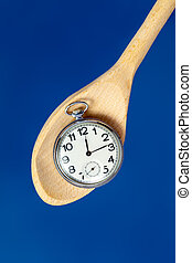 pocket watch on a wooden spoon