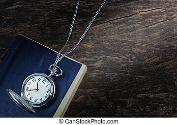 Pocket watch on an old book, a notebook.