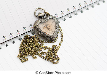Pocket watch placed on the booknote. Heart shape.