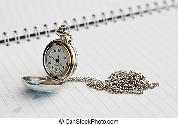 Pocket watch placed on the booknote. Silver.