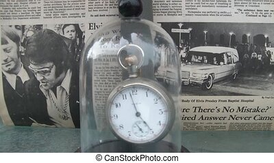 Era abstract of pocket watch behind glass and then lifted while watch rocks back and forth with newspaper of Elvis' death in background.
