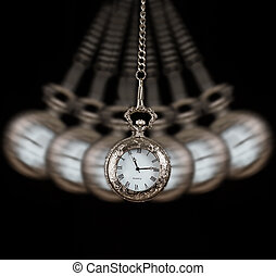 Pocket watch swinging on a chain black background