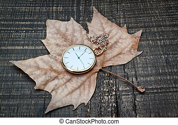 Pocket watch the autumn leaves. On a wooden texture.