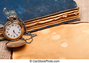 Old pocket watch with antique book and paper on burlap background.