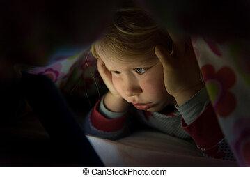 poco, niño, en, manta, mirar fijamente, en, encendido, tableta, pantalla