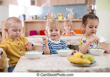 poco, niños comer, en, jardín de la infancia
