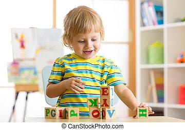 poco, preschooler, chico niño, juego, con, juguete, cubos, y, memorizar, letters., educación temprana, concepto