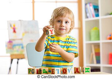poco, preschooler, niño, niño, juego, con, juguete, cubos, y, memorizar, letters., educación temprana, y, preescolar, concepto