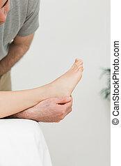 Podiatrist examining the foot of his patient
