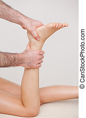 Podiatrist manipulating the ankle of his patient in a room