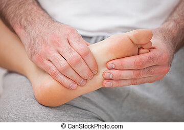 Podiatrist massaging the foot of a woman while holding it on his thigh indoors