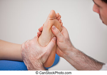 Podiatrist practicing reflexology on the foot of woman in a...