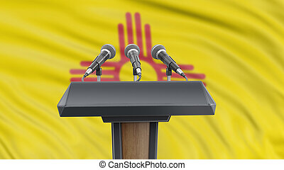 Podium lectern with microphones and New Mexico flag in background