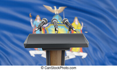 Podium lectern with microphones and New York flag in background