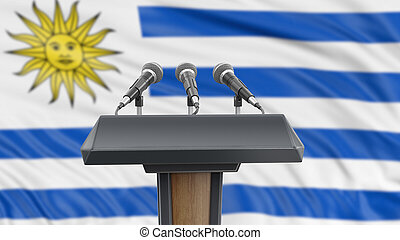 Podium lectern with microphones and Uruguayan flag in background