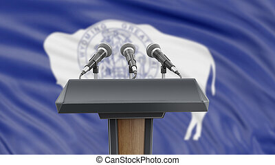 Podium lectern with microphones and Wyoming flag in background