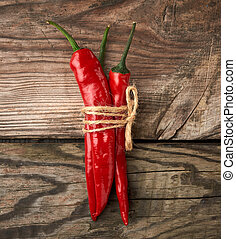 pods of red chili peppers tied with a brown rope