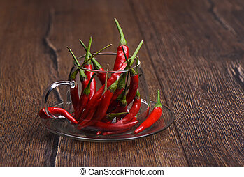 Pods of red hot pepper in a glass mug on a wooden background.