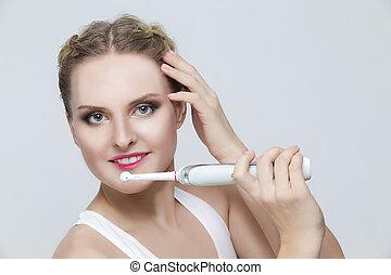 poetsen, blonde , toothbrush., verticaal, witte , vrouw, bustehouder, elektrisch, op, teeth, kaukasisch, achtergrond.