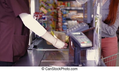 Point of sale.Cashier scans purchase products - Cashier...
