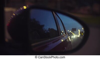 Defocused city lights at night in rearview mirror - Point of...