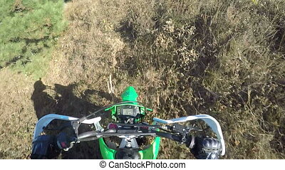 Point of View: Enduro racer on dirt bike riding off-road through the forest