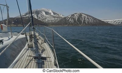 Point of view from sailing yacht in sea and mountains with snowy peaks