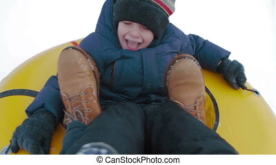Point of view Happy little boy is sledding in mountain through the snow flies on a springboard in slow motion