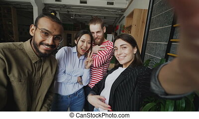 Point of view of happy multi-ethnic team taking selfie in...