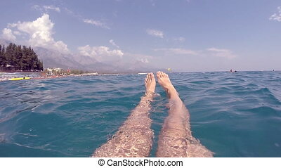 Point of view of man is lying on sea water completely relaxed. Male feet swimming at ocean during summer vacation. POV Close up Slow motion