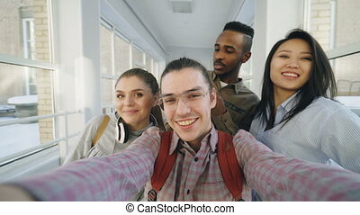 Point of view of positive multi-ethnic group of friends talking selfie photos holding smartphone and having fun while standing in corridor of university