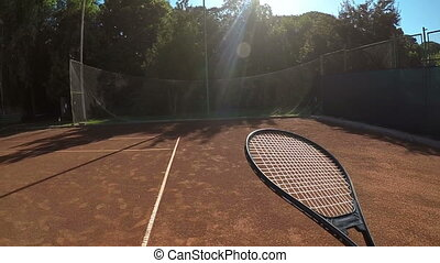 Point of view of tennis player balances ball on racket