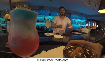 Point of view of waiter delivering drinks on tray at fancy...