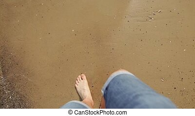 Point of view of young man stepping at the golden sand at sea beach. Male legs walking near ocean. Bare foot of guy going on sandy shore with waves. Summer vacation or holiday .