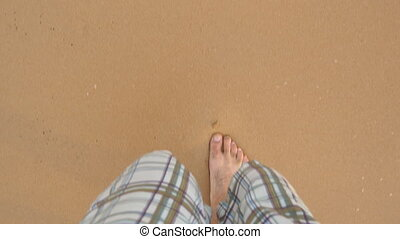 Point of view of young sporty man running at the golden sand at sea beach. Male legs of athlete jogging near ocean. Bare foot of guy going on sandy shore. Healthy active lifestyle. Close up POV