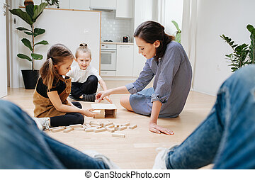 Point of view photo. Father looks how mom and kids playing with wooden blocks