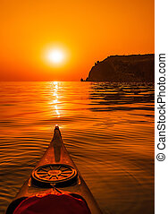 Point of view shot from inside kayak on calm sea and red burning sunset in the background. A kayak alone when the sun goes down and the view on the headlands of cliffs turns red